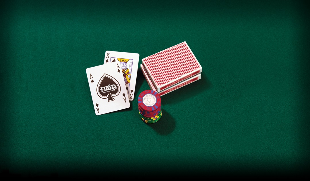 Ace and King of Spades with a stack of chips and two decks of cards on a green felt table
