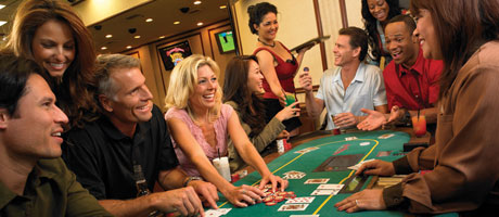 Several people enjoying a table game inside a casino
