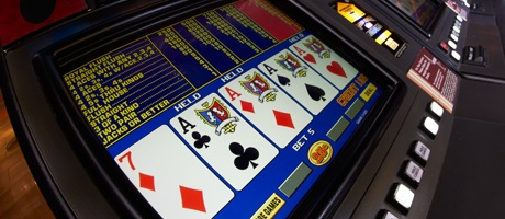 Video poker terminal showing four of a kind Aces with a 7 of diamonds